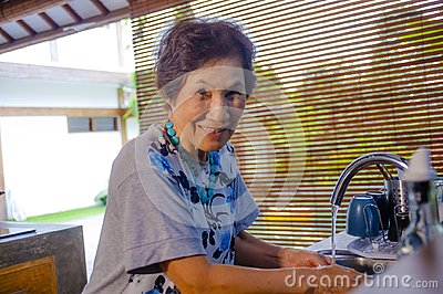 lifestyle portrait of senior happy and sweet Asian Japanese retired, woman cooking at home kitchen alone neat and tidy
