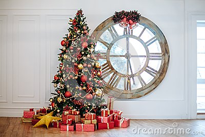 Beautiful Christmas living room with decorated Christmas tree, gifts in front of whate wall. New year tree with red and gold decor