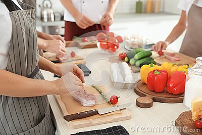 Group of people preparing meat at cooking classes