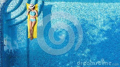 Beautiful young girl relaxing in swimming pool, swims on inflatable mattress and has fun in water on family vacation