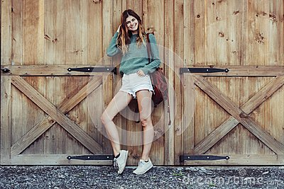 Happy woman with long legs look to the side near barn on the farm wearing casual outfit with shorts, backpack and sneakers.