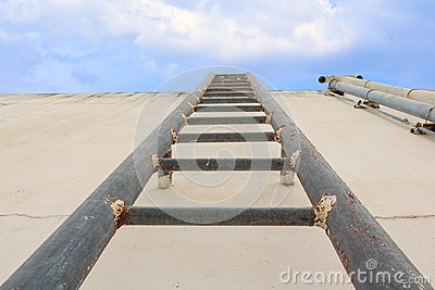 Stair old vertical industrial metal rusted to Water tank no safety rails on blue sky background
