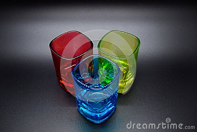 Three multicolored shot glasses on black background