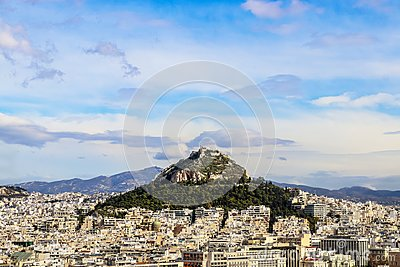 Looking over the rooftops to Lycabettus Hill - the highest spot in Athens Greece with church of St George and a resturant where to