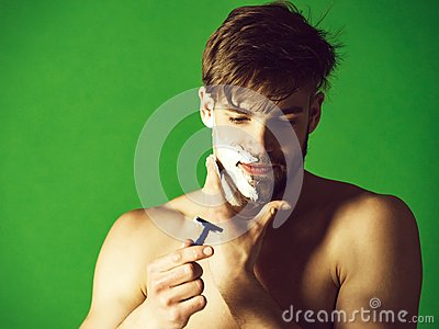 Man shaving beard hair with safety razor and foam