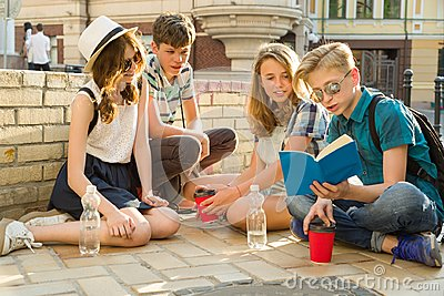 Happy 4 teenage friends or high school students reading books. Friendship and people concept