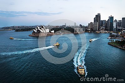 Cityscape of Sydney with Opera house and ferry boats in the ocean after sunset, Sydney, Australia