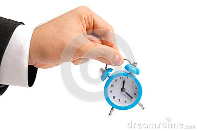 A businessman is holding an alarm clock. Watch in hand. The concept of hourly pay, time. Late for work. Full or incomplete rate. O