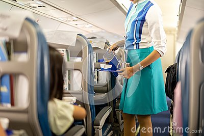 stock image of flight attendant serving drinks to passengers on board.
