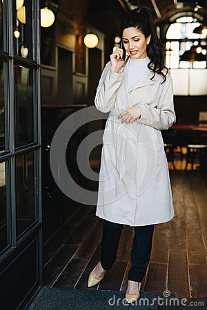 Full length portait of elegant businesswoman wearing white overcoat, stylish shoes and black trousers standing in cafe calling he