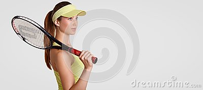 Sideways shot of thoughtful woman has healthy clean skin, keeps racquet on shoulder, wears tennis cap, thinks about future game, s
