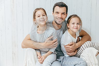 Father and kids. Paternity concept. Handsome unshaven affectionate dad embraces his two pretty dauhters, going to have walk