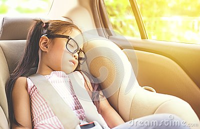 Girl sleeping in child car seat.