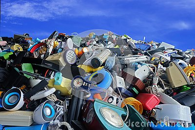 stock image of pile of used electronic and housewares waste division broken or damage with blue sky and clouds background