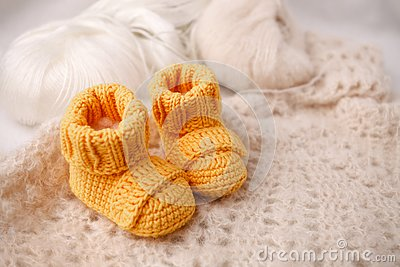 Children`s yellow knitted booties on a light gentle background. The concept of expecting a child, motherhood, parenthood