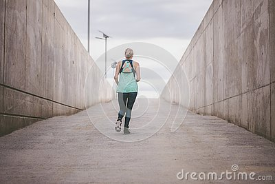 Young woman running away in an industrial scene, during sunrese.