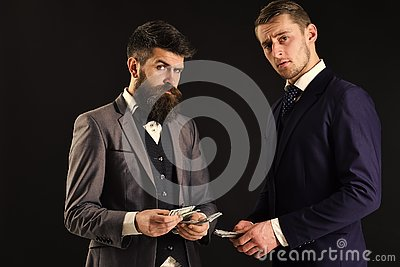 Meeting of reputable businessmen, black background. Man with beard on serious face counting money, pay to partner