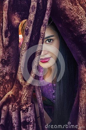 Mysterious woman,Beautiful woman with long dark hair and red lips resting in the tree roots and looking at you.