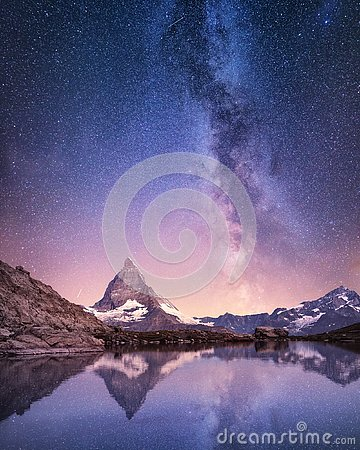 Matterhorn and reflection on the water surface at the night time. Milky way above Matterhorn, Switzerland.