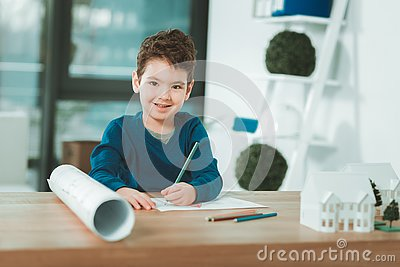 Positive talented boy holding pencils