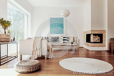 Beige and white textiles and a modern spherical pendant light in a sunny, tranquil living room interior with natural decor.