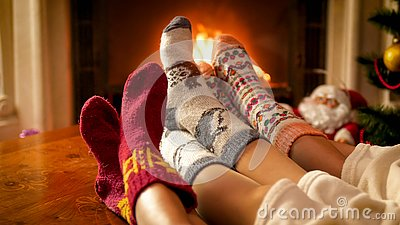 Closeup toned image of family in knitted socks warming by the fireside on Christmas eve
