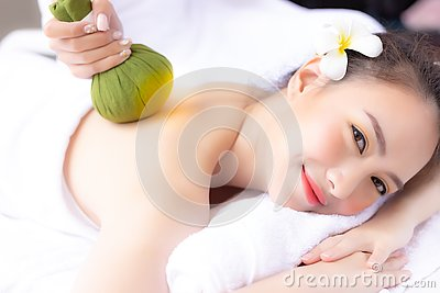 Massager rejuvenate and massage charming beautiful woman's back by using herbal ball. Attractive girl feels relaxed and happy.