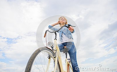 Girl rides bike sky background. Woman rent bike to explore city copy space. Bike rental shops primarily serve people who