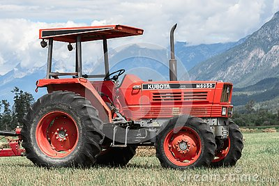 Farm tractor in a hay field against the Rocky Mountains