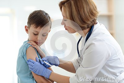 Brave boy receiving injection or vaccine with a smile