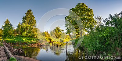 summer evening landscape. View of the river with overgrown coastlines from the old bridge to the light of the setting sun