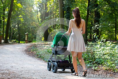 Back view of attractive woman walking with stroller in the natural forrest walkway, young mother is outside with her newborn baby