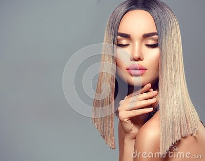 Fashion hairstyle. Ombre dyed hair. Beauty Model girl with perfect healthy hair and beautiful makeup posing in studio
