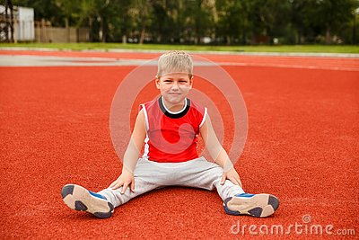 Seven-year-old boy in a sports uniform sits on the red surface of the stadium