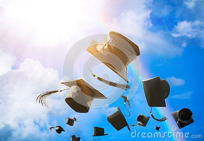 Graduation caps, hat thrown in the air with sun ray blue sky abs