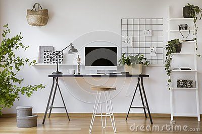 Hairpin stool standing by the wooden desk with mockup computer screen, metal lamp and coffee cup in real photo of white home offic