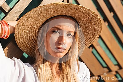 Portrait of attractive young blond woman 20s in straw hat and sw