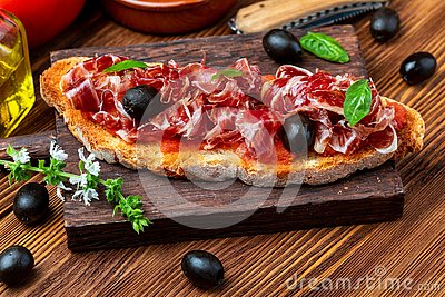 Delicious bread toast with natural tomato, extra virgin olive oil, Iberian ham, black olives and basil leaves.