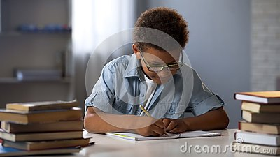 Clever male pupil doing math homework, solving equation in notebook, knowledge