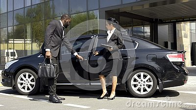Car showroom consultant showing luxury car to buyer, vehicle leasing business