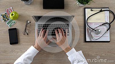 Medical worker typing on laptop, keeping electronic medical records, top view