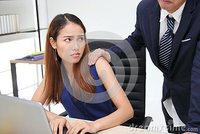 Angry unhappy Asian secretary woman looking hand`s boss touching her shoulder in workplace. Sexual harassment in office