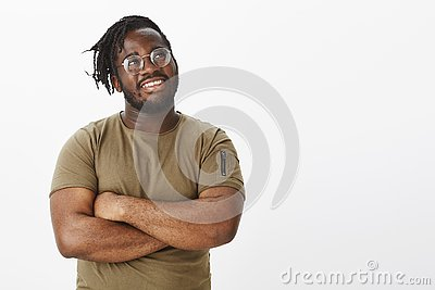 Guy feeling proud finishing work in time. Happy dreamy african american plump man with beard in t-shirt and glasses