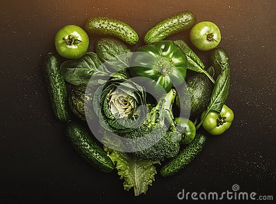 Heart shape form by various green healthy vegetables, top view