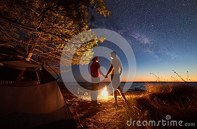 Young couple man and woman having rest at tourist tent and burning campfire on sea shore near forest