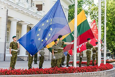 VILNIUS, LITHUANIA - AUGUST 22, 2018: Europ Union flag and Lithuanian flags rising up by Lithuanian soldiers in Daukantas square n