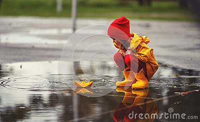 Happy child girl with umbrella and paper boat in puddle in a