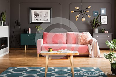 Wooden coffee table with tea cup and open book standing on carpet in dark living room interior with powder pink lounge with fur c