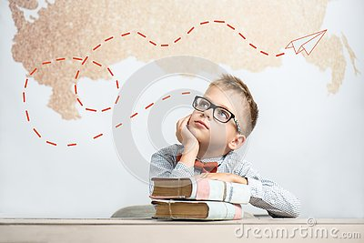 A thoughtful schoolboy sits at a desk with books