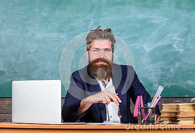 Teacher formal wear sit table classroom chalkboard background. Pay attention to details. Teacher concentrated bearded